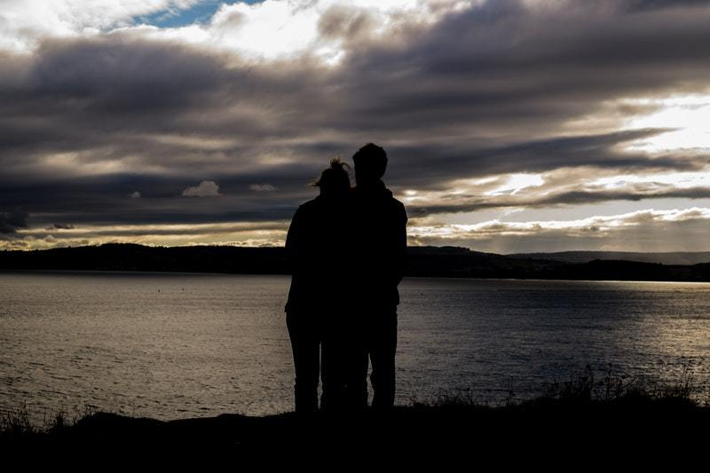 silhouette of couple hugging in front of lake