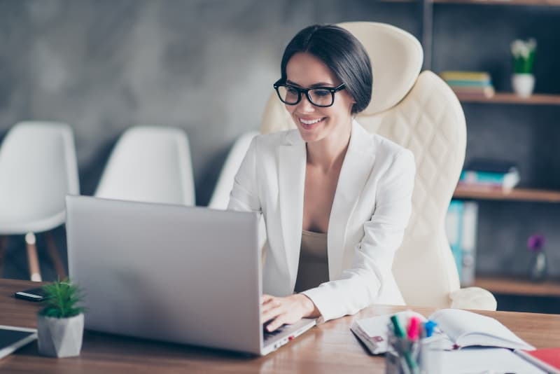 smiling business woman typing on her laptop