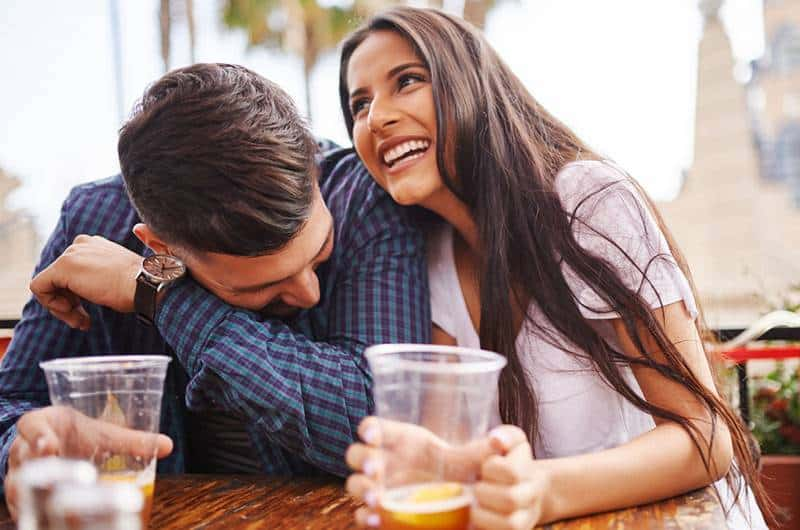 smiling couple drinking beer form plastic glass