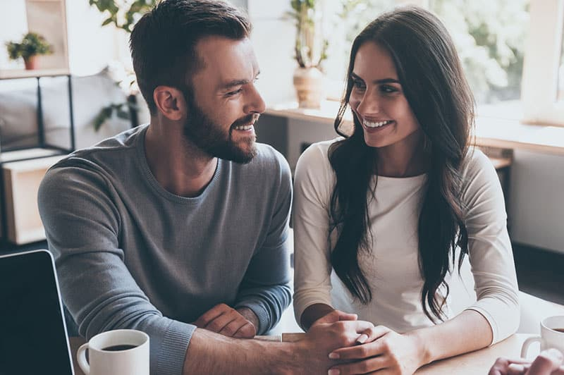 smiling couple looking at each other at cafe