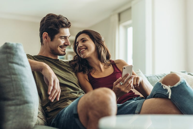 smiling couple sitting on the couch and looking at phone