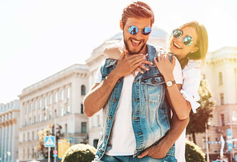 smiling couple with sunglasses outside