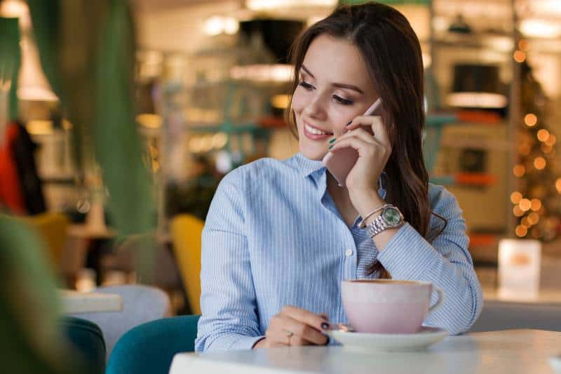 smiling girl talking on her phone at cafe