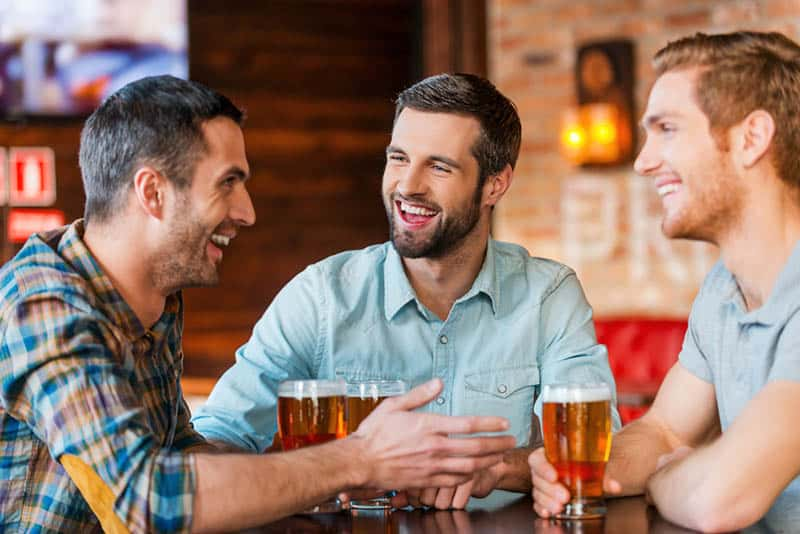 smiling male friends talking and drinking beer