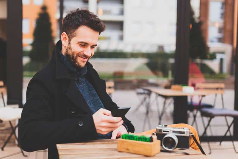 smiling man wearing black coat and typing on his phone at street cafe