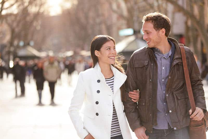 smiling woman holding a man and looking each other while walking on street