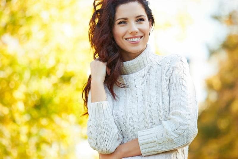 smiling woman in sweater outside