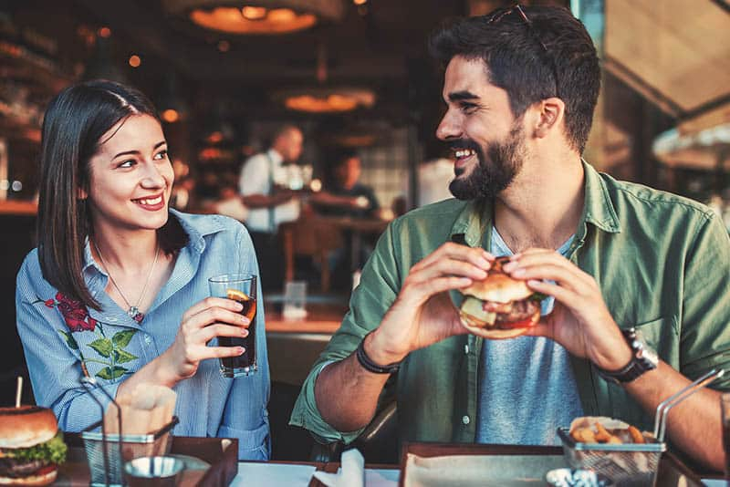 smiling young couple looking each other in restaurant