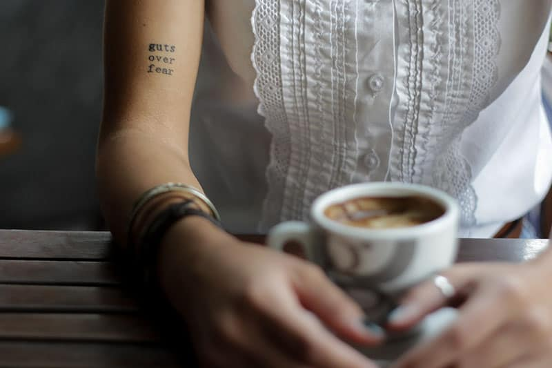 tattoo quote on woman arm