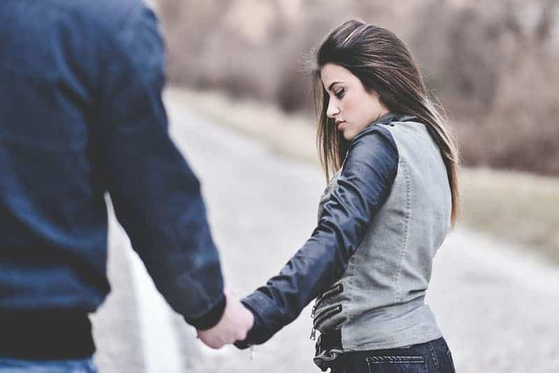 thoughtful woman holding man hand