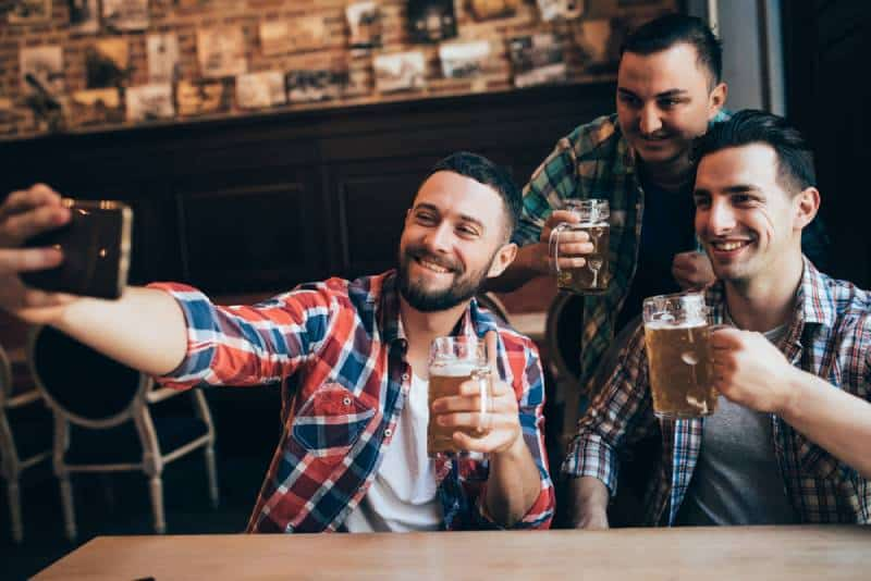 three male friends taking selfie while holding beer
