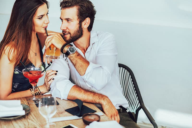 woman and man flirting and drinking coctail