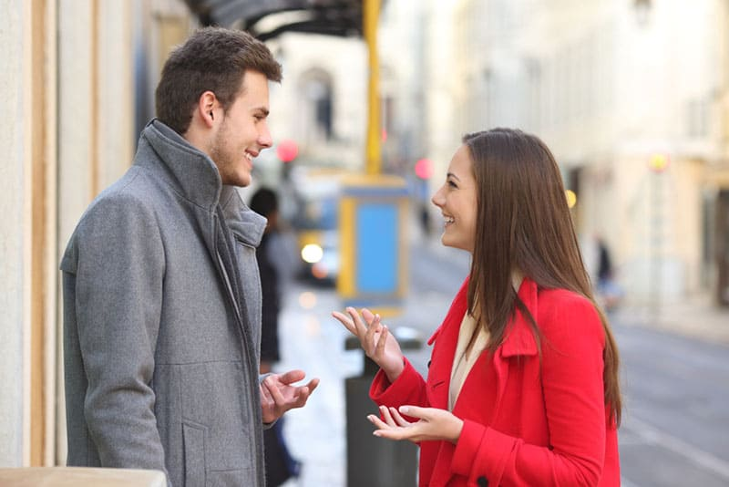 woman in red coat talking to man
