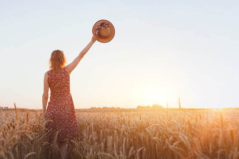 woman raises her hat at field