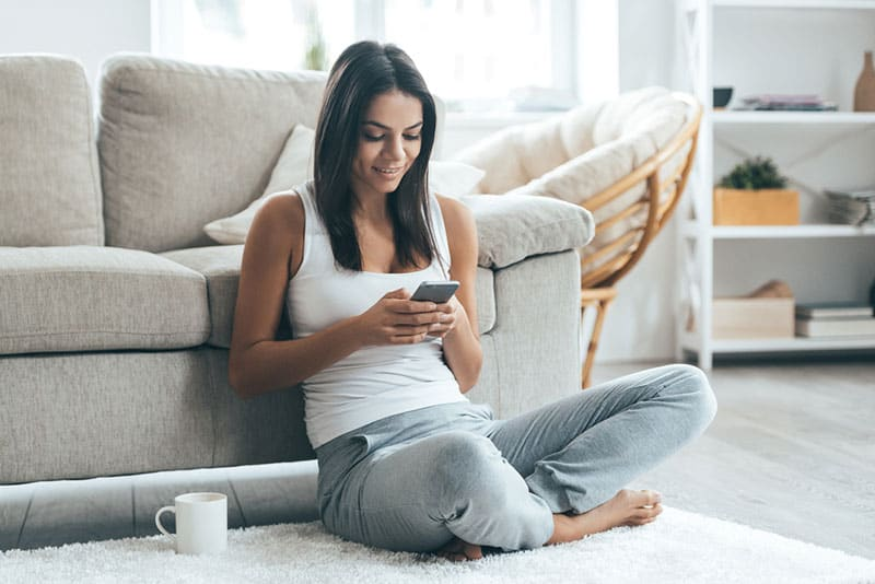 woman sitting on floor and texting