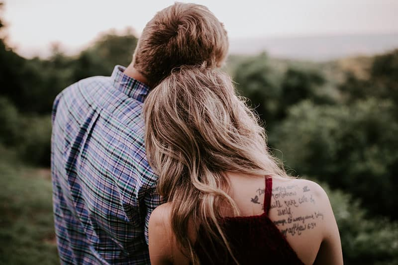 woman with tattoo standing with her man outdoor
