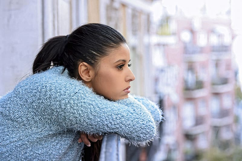 worried woman leaning on balcony fence