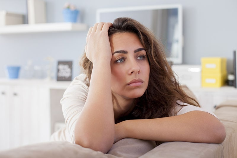 worried woman looking at distance in the living room