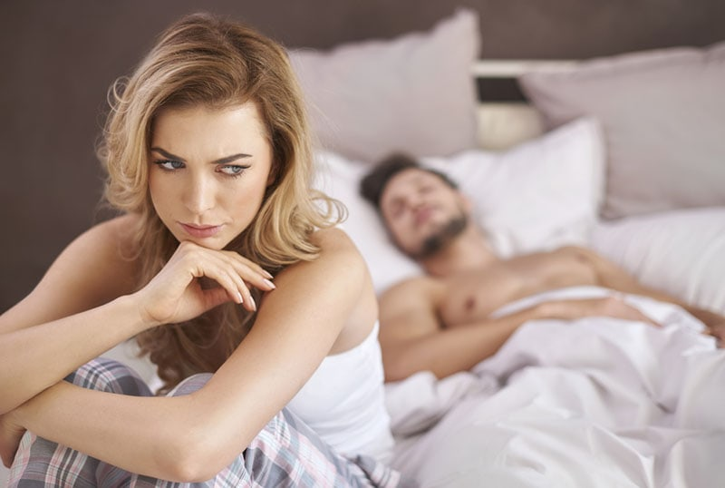 worried woman sitting on the bed while man sleeps