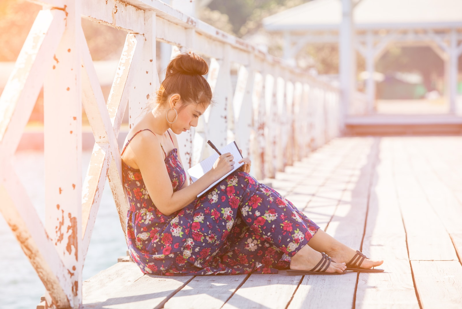 young woman sitting on the bridge and writing in the notebook