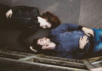 couple lying on concrete surface and looking each other