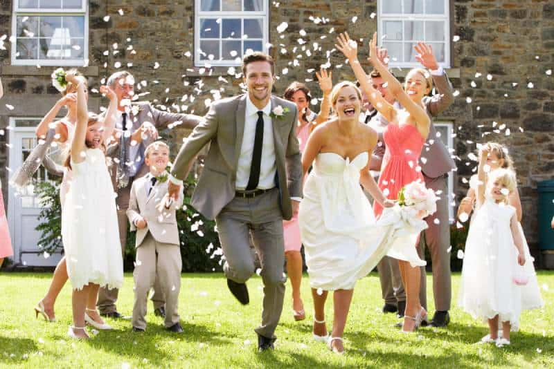 Guests throw confetti over bride and groom