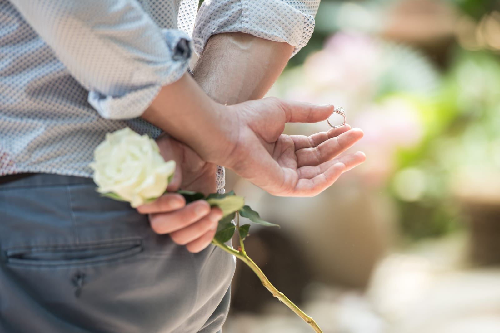 Men hide the ring and white rose behind with surprise
