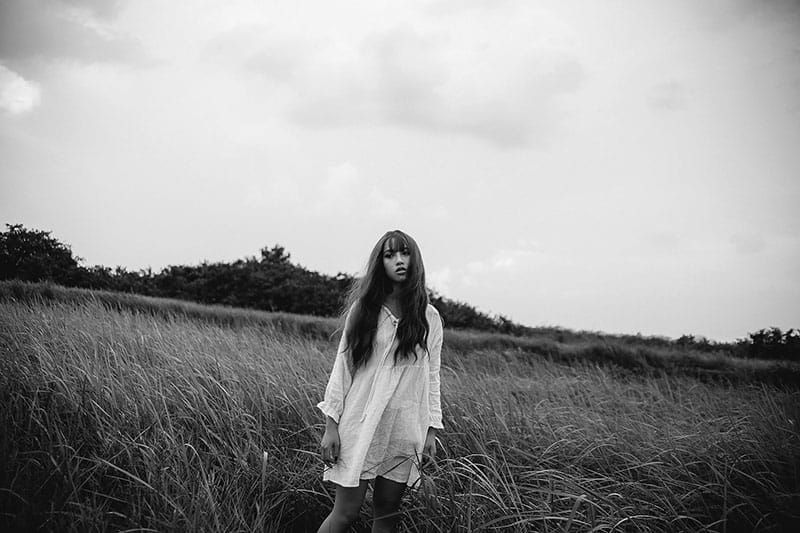 sad woman standing outdoor in white dress