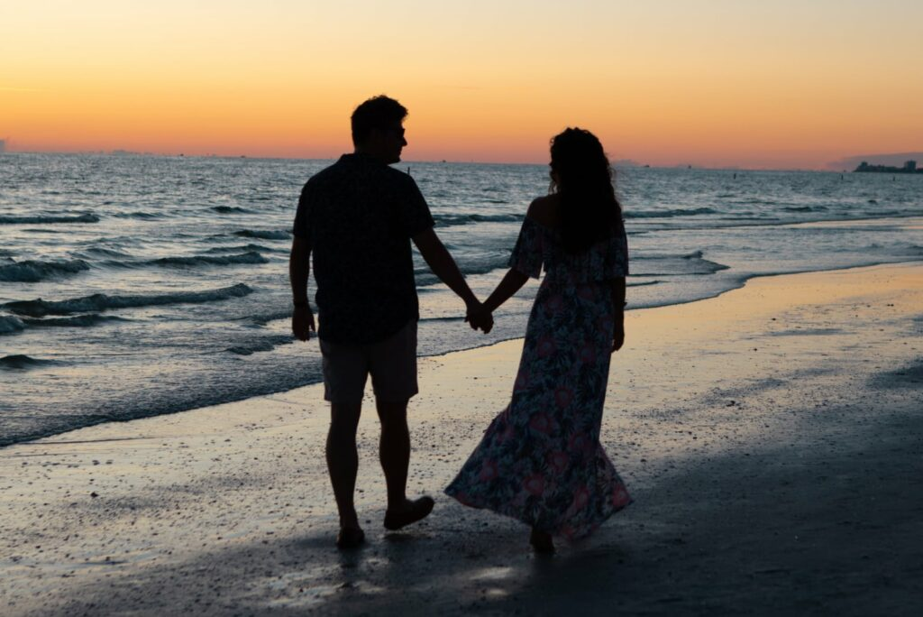 a couple holding hands and walking along the beach
