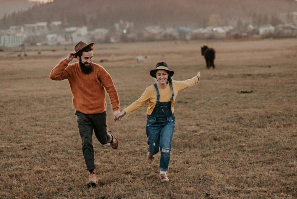 a girl running across a field with a boyfriend