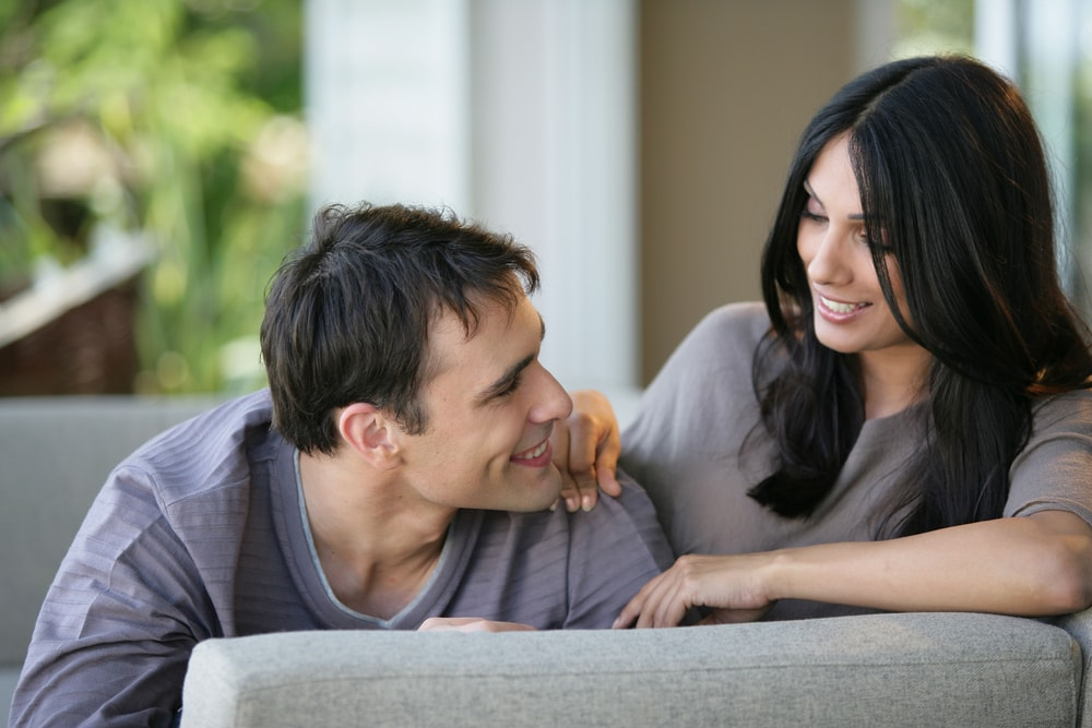 a smiling loving couple sitting on the sofa and looking at each other