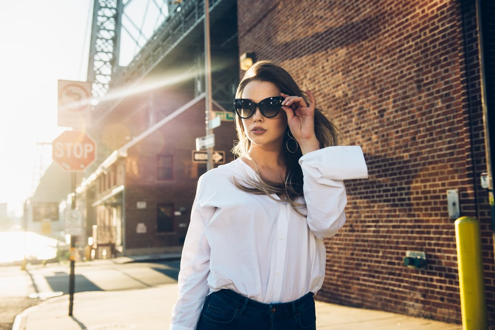 attractive brunette with sunglasses and in a white shirt walks down the street