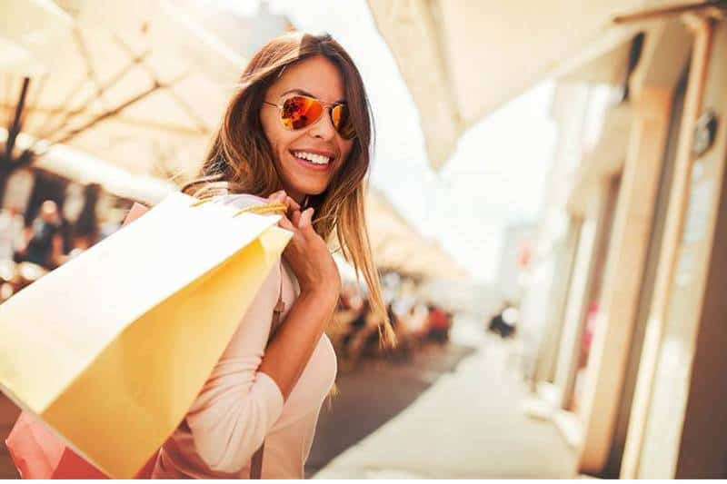 beautiful smiling woman wearing sunglasses and holding shopping bag