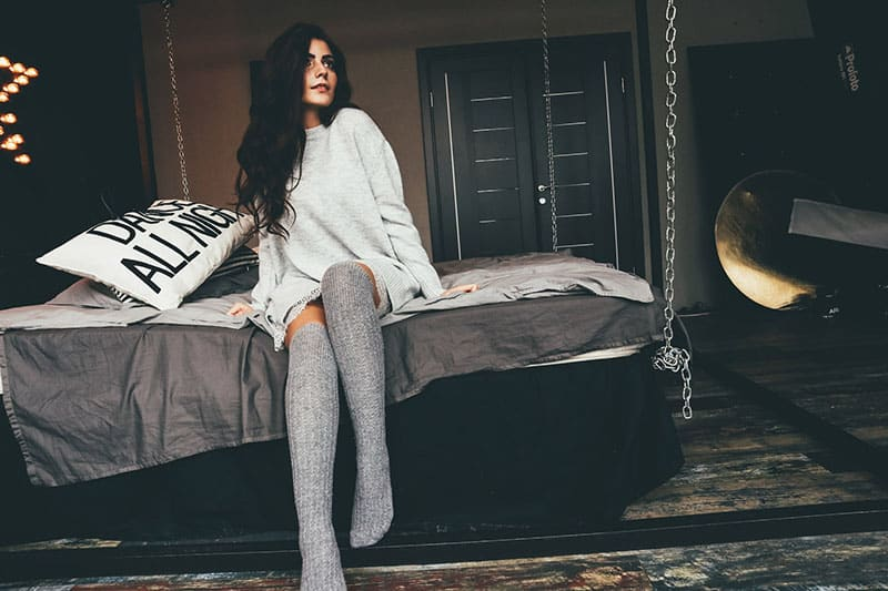 beautiful woman in sweater sitting on the bed