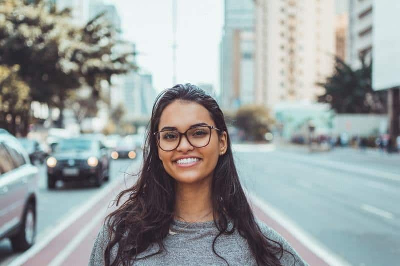 beautiful young smiling woman standing on street and wearing eyeglasses