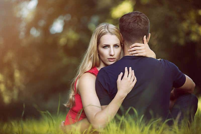blond serious woman hugging man on the grass