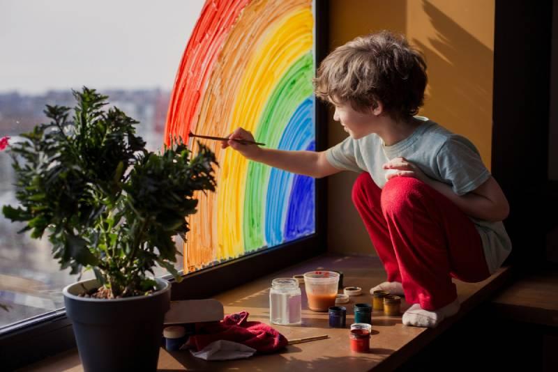 child drawing rainbow on window