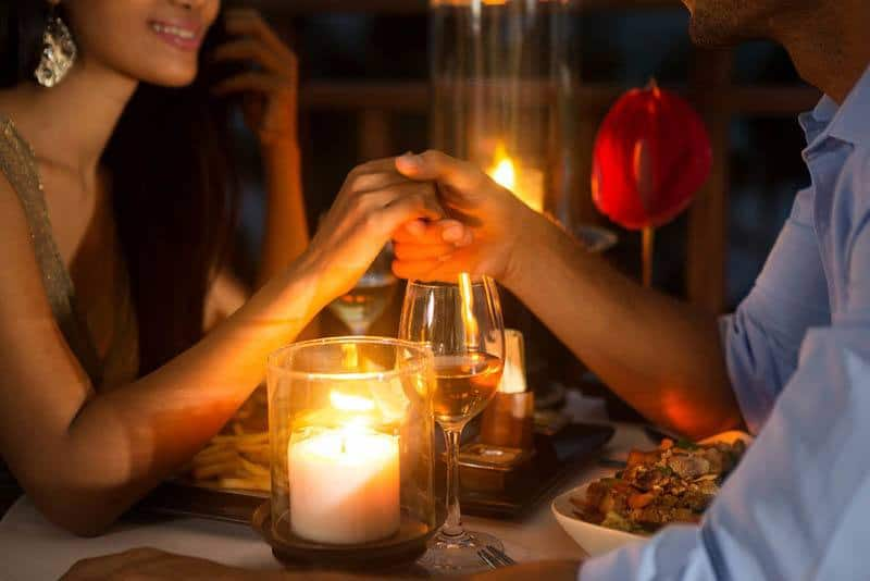 close up photo of couple having date dinner and holding hands