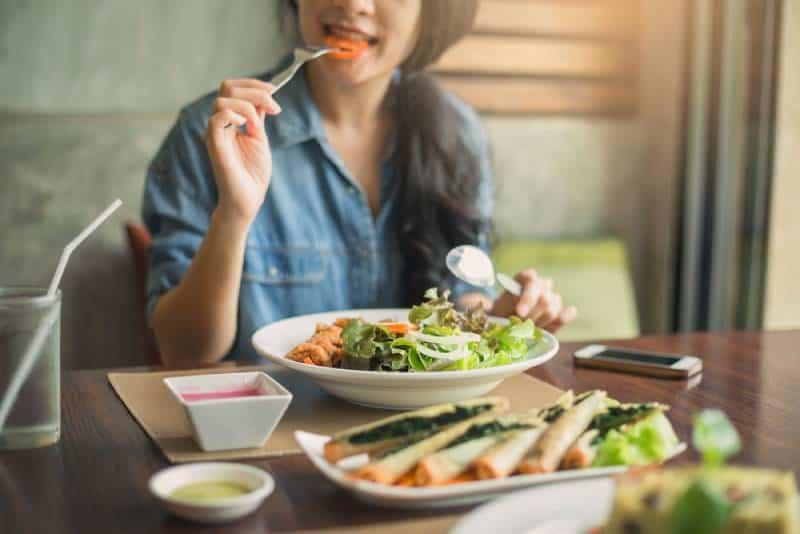 closeup of a woman eating salad