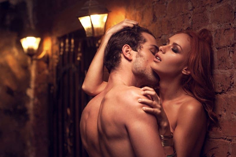 couple kissing passionate while standing by the wall