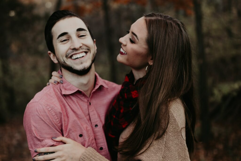 embracing a smiling couple in the woods