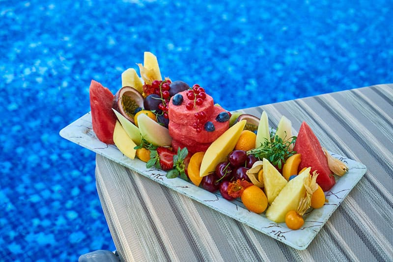 fruits on plate by the pool