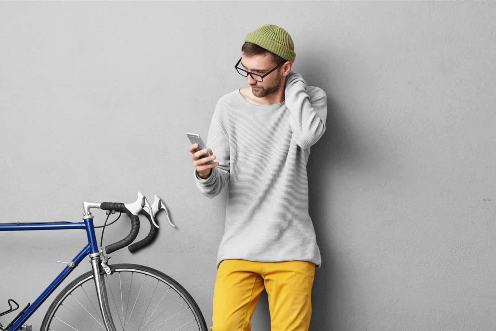 guy wearing stylish glasses while reading sms