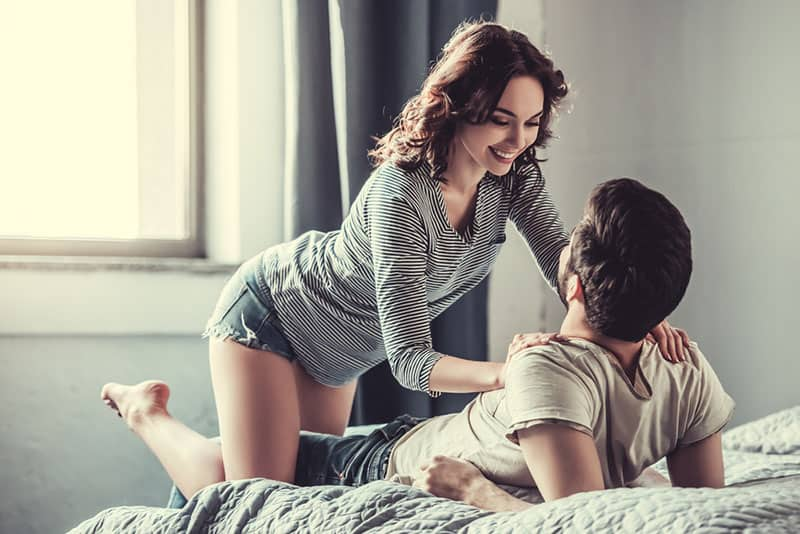 happy woman playing with man on bed