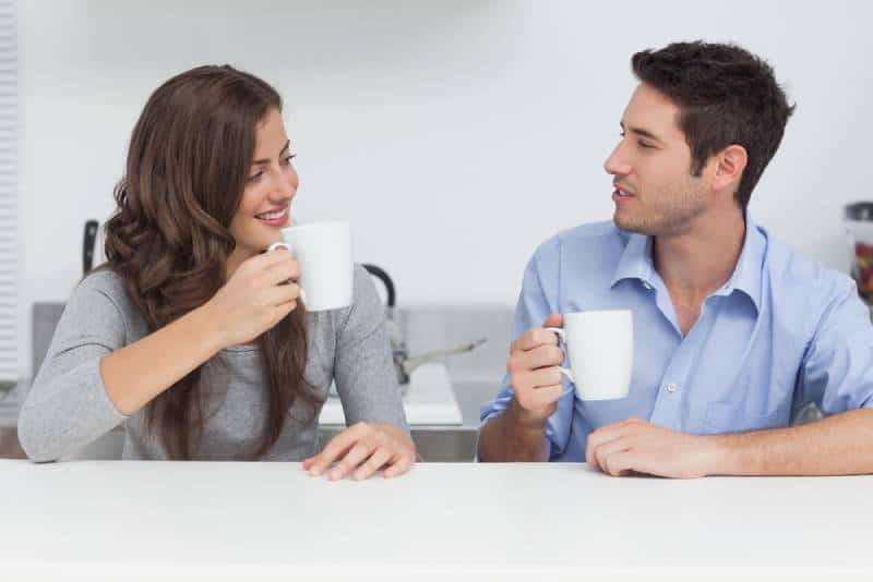 male and female talking and holding white cup of tea at home