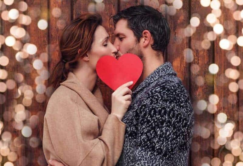 man and woman kissing while woman holding paper shape of heart