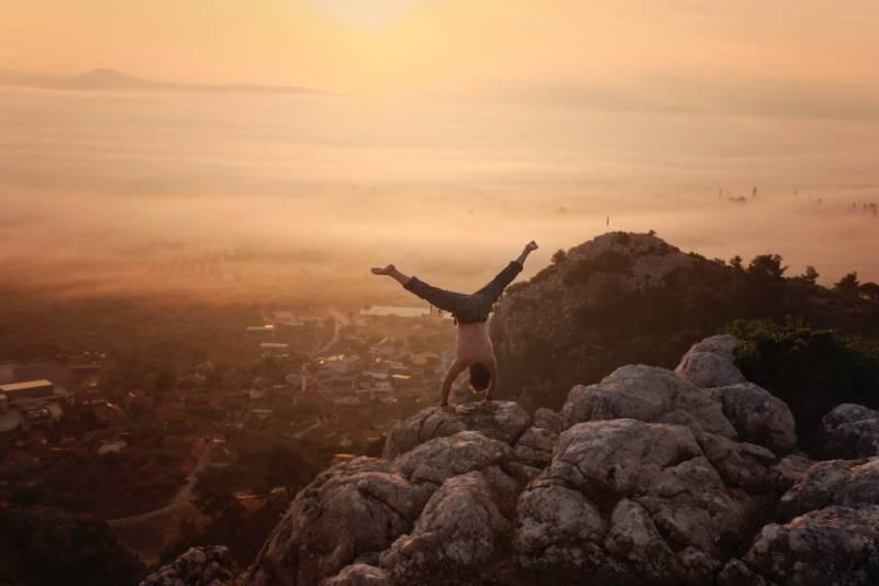man doing handstand on boulders