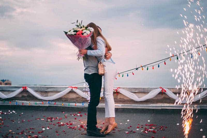 man hugging proposed woman