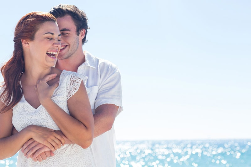 man hugging smiling woman on the beach