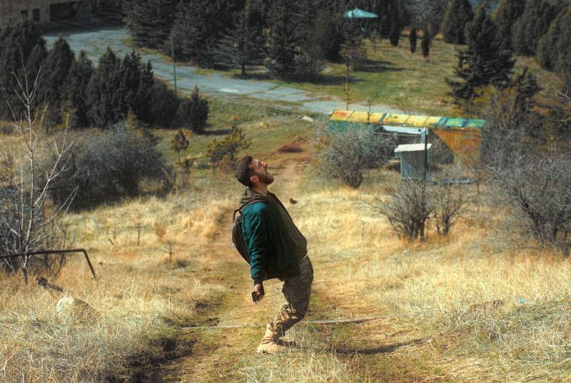 man in green jacket walking on brown field during daytime